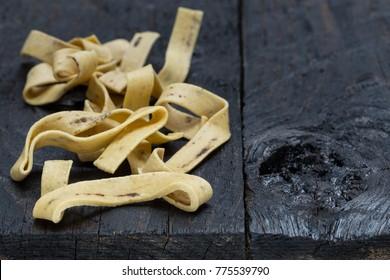 Tagliatelle with cep on dark rustic wood.