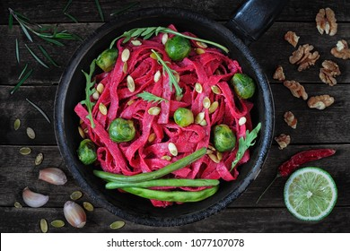Tagliatelle pasta with beet pesto sauce, Brussels sprout and green beans over dark wooden background, top view