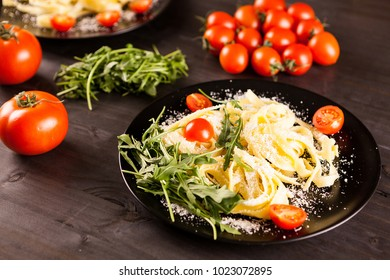 Tagliatelle pasta in black plate with parmesan and cherry tomatoes