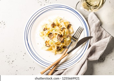 Tagliatelle pasta with black truffles and parmesan cheese. Plate captured from above (top view, flat lay). Grey stone background. Layout with free text space.
