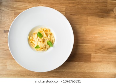 tagliatelle pasta with cheese and basil on a wooden table. Top view