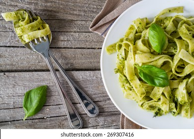 Tagliatelle pasta with pesto sauce and basil leafs on white plate, wood background, top view