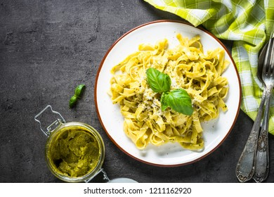 Tagliatelle pasta with pesto sauce and parmesan cheese on black stone table. Top view, copy space.