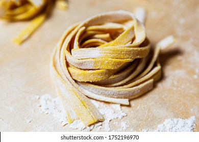 Tagliatelle pasta preparation.Traditiona Italian tagliolini cooking for dinner in restaurant kitchen on wooden table surface in white flour powder