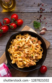 Tagliatelle pasta with salmon and creamy sauce on frying pan