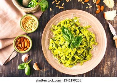 Tagliatelle pesto sauce ready to eat flat lay top view on dark wooden table rustic style - Italian vegetarian pasta with green dressing and all ingredients of the recipe around the dish - Image