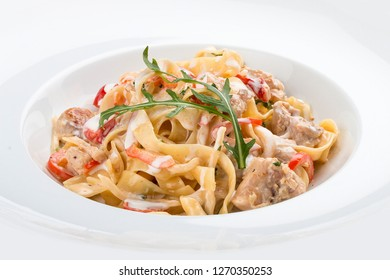 Tagliatelle with rabbit and pepper, with cream sauce in a white plate. On textile background