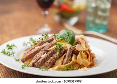 Tagliatelle with steak stripes on a plate