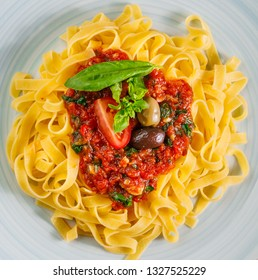 tagliatelle with tomato sauce, olives,  and basil leaves on rustic glazed clay plate