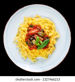 Tagliatelle with tomato sauce, olives, capern and basil leaves on rustic glazed clay plate - isolated on black background