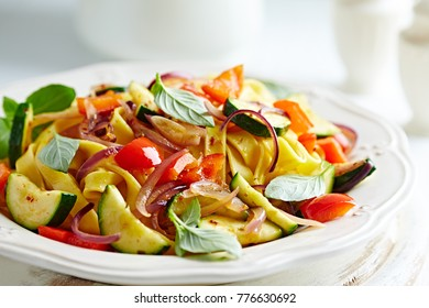 Tagliatelle with zucchini, red pepper, red onion and fresh basil.  Italian food. Italian cuisine. Symbolic image. Concept for a tasty, vegetarian dish. White rustic wooden background. Close up.