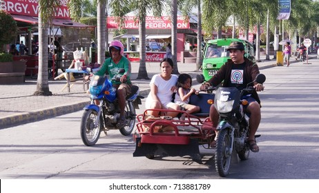 TAGUM CITY, PHILIPPINES—FEBRUARY 2016: Passengers riding a motorcycle with a sidecar, called trisikad which is a popular public transportation in the Philippines.