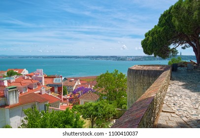 Tagus river and old houses of Alfama district of Lisbon city, Portugal, as viewed from hill of Saint George Castle.