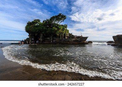 Tahah Lot Temple and ocean waves at sunny day, Bali, Indonesia