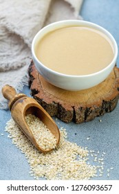 Tahini in a bowl and a wooden scoop with sesame on textured gray background, selective focus.