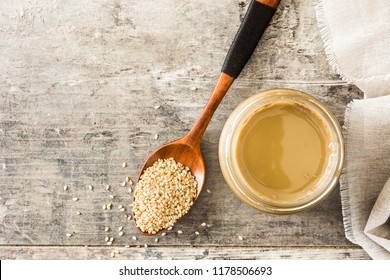 Tahini and sesame seeds on wooden table.Top view Copyspace