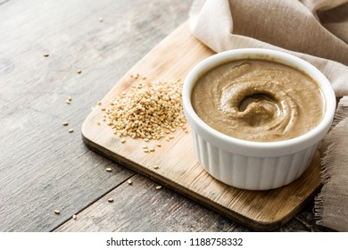 Tahini and sesame seeds on wooden table. Copyspace