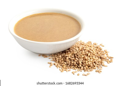 Tahini in a white ceramic bowl next to a pile of sesame seeds isolated on white.