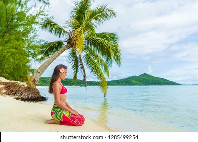 Tahiti Bora Bora French Polynesia Beach Vacation Travel Holidays. Woman relaxing sitting down on paradise beach on Matira Beach, Bora Bora. Happy girl wearing traditional pareo and Bikini in Tahiti