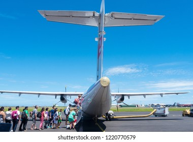Tahiti, French Polynesia - January 10 2016: A row of people board a small plane at the FAAA International Airport at Papeete.