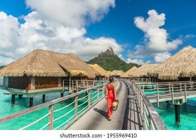 Tahiti luxury hotel honeymoon travel vacation tourist woman walking at luxury resort in overwater bungalows villas. View of Mount Otemanu, Bora Bora, French Polynesia
