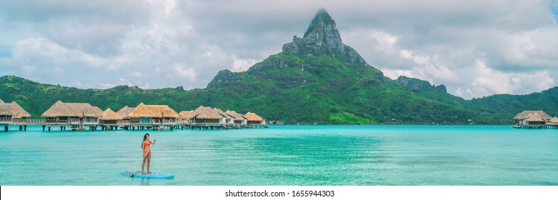 Tahiti luxury resort vacation in Bora Bora island, French Polynesia summer travel header landscape. Woman tourist doing stand up paddleboard, leisure recreational watersport at hotel panoramic.
