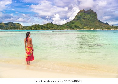 Tahiti luxury travel beach vacation woman walking in polynesian cover-up skirt beachwear on idyllic paradise island in French Polynesia. Red traditional outfit,, bikini and flower girl.