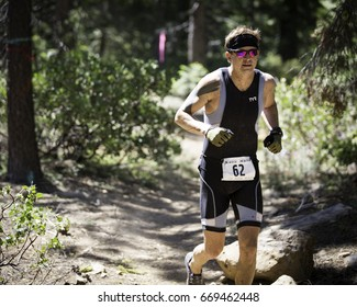 Tahoe City, CA, USA - June 24, 2017: Matthew Monnot from San Francisco runs the trails at XTERRA Tahoe City.