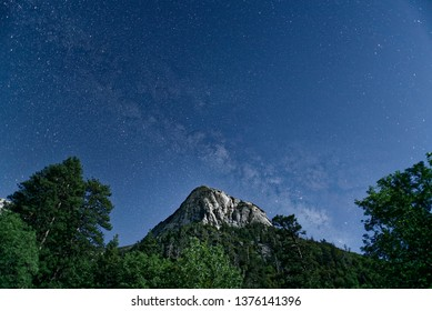 Tahquitz Rock looms above the town of Idyllwild California on a moonlight night with the milky way visible in the night sky