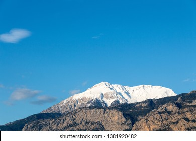 Tahtali peak and Taurus mountains chain at the first hour after sunrise. Mild sinlight, serene blue sky with  clouds. Treed and rocky slopes.