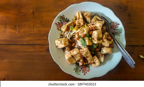 tahu kupat solo is Indigenous snack of warm salad of rice cake, beancurd, tofu and vegetable from solo, Central Java. Plated on ceramic plate; topped with crusted spicy peanuts and crackers on top