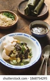 Tahu Tek or Tahu Lontong is popular Surabaya street food, consist of fried tofu, omelette, rice cake, bean sprout, shrimp crackers with savory peanut sauce from petis (shrimp paste)