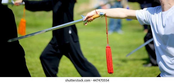 Tai Chi martial arts athlete expert makes motions with sharp sword