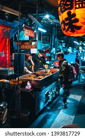 Taichung, Taiwan - 10.04.2019: A boy is buying a night snack at a street food stall at a night market in Taichung.