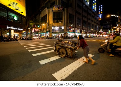 Taichung, Taiwan - 4 Mar 2019: An old lady in the middle of a Taichung's crossroads. Taichung is one of the largest cities of Taiwan