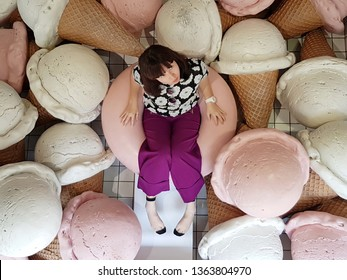 Taichung,Taiwan-19 March 2019: Asian woman sits and plays at a dreamy cute pool situated in a popular ice cream shop in Taichung. Pool decorates with giant scoops of white and pink ice cream cones.