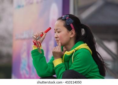 TAIHU,WUXI,CHINA-MAY 20:Unidentified chiness girl look at face on telephone on May 16,2016 in Taihu lake,Wuxi,China.