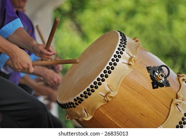 Taiko Drummer in Action - focus on drum, hands/sticks in motion - drum head vibrating