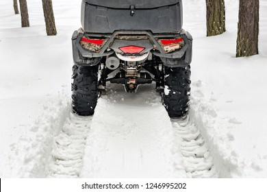 Tail of ATV 4wd quad bike in forest at winter. 4wd all-terreain vehicle stand in heavy snow with deep wheel track. Seasonal extreme sport adventure and trip