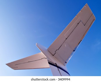 Tail of a business jet reaches into a blue sky