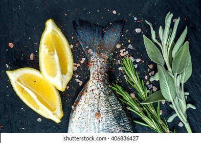Tail of fresh raw Dorado or sea bream fish on black slate stone board with spices, herbs, lemon and salt. Top view