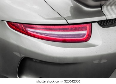 Tail light of sport grey car with rain drops and shadows. Closeup headlights of car. Modern luxury car close-up banner background. Concept of expensive, sports auto Closeup headlights Porsche 911