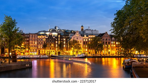 Tail lights of boats crossing canals of Amsterdam at dusk time and apartments illuminated by street lights.