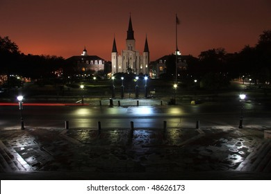 Tail lights on Decatur street in front of Jackson Square silhouetted by the lights of Bourbon Street in the French Quarter of New Orleans, LA