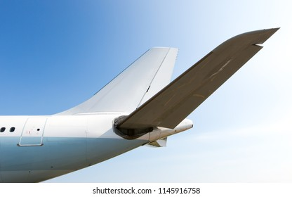 Tail of a passenger plane close-up. Blue sky in the background.