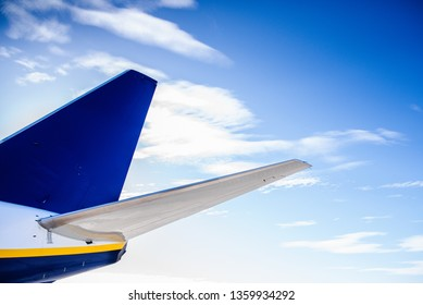 Tail of a plane of a travel company, isolated with blue cloud background, no logos.