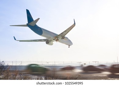 Tail view of landing airplane. Aircraft flying over highway.  Road with high traffic near airport runway. Type of transport comparison.  Travel concept.