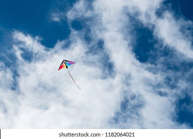 Tailed kite flying in with clouds and blue sky in background.