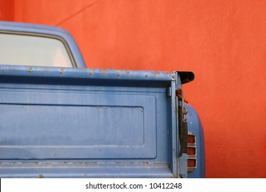 The tailgate of a blue battered sixties American Pickup Truck in front of a red wall