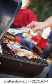 Tailgate: Man Grilling Sausages And Shrimp For Football Party